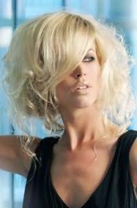 Стрижка с косой челкой на средние волосы волнистого типа для блондинок гармонирует с повседневным макияжем с акцентом на голубые глаза