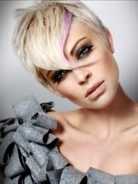 Короткая стрижка с удлиненной челкой и цветом волос блонд, дополняется сиреневой колорированой прядью и гармонирует с макияжем смоки айс и помадой естественного бежевого оттенка