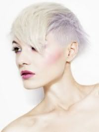 Креативная короткая асимметричная стрижка с платиновым цветом волос, подчеркнутым светло-фиолетовым колорированием, сочетается с естественным макияжем глаз, румянами розового оттенка и помадой цвета фуксии