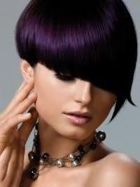 Креативная асимметричная стрижка на короткие волосы цвета баклажан с косой челкой дополняется макияжем, состоящим из черной туши, персиковых румян и блеска для губ, которые идеально подчеркивают холодный тип внешности