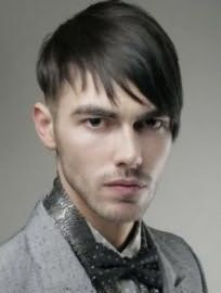 Асимметричная мужская стрижка с выбритыми висками и удлиненной челкой на один бок гармонирует с темно-русым цветом волос прямого типа и карими глазами
