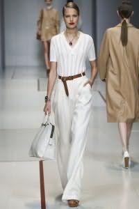 Брюки белого цвета широкого силуэта дополняются вязаной блузой от Trussardi.