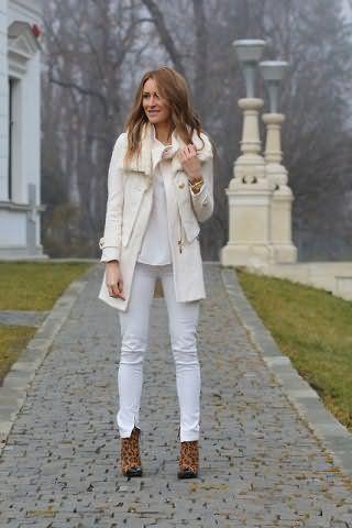 Брюки белого цвета, облегающего фасона, монохромно сочетаются со свободной майкой и тонким пальто.