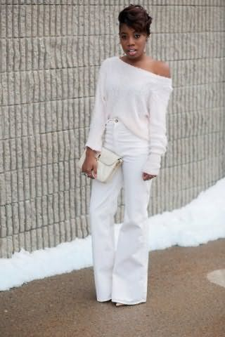 Брюки белого цвета, расклешенного покроя монохромно дополняются тонким свитером широкого фасона.
