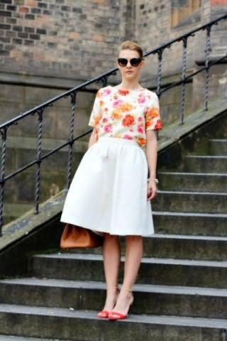 Юбка белого цвета, расклешенного фасона, длиной до колен в тандеме с блузкой с флористическим орнаментом.