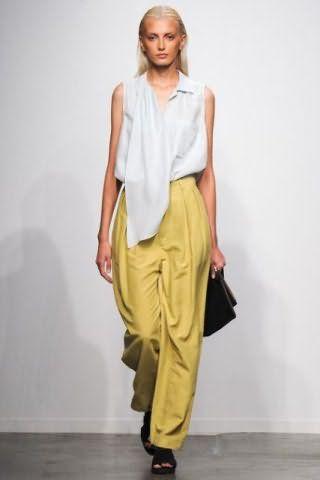 Асимметричная рубашка белого цвета с серым подтоном гармонирует с брюками горчичного оттенка от Creatures of Comfor.