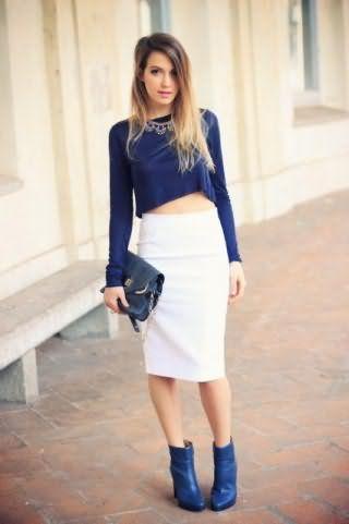 Юбка белого цвета, прямого покроя, длиной до колен в тандеме с укороченной блузкой темно-синего оттенка.