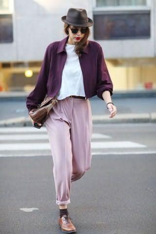 Короткая майка белого цвета дополняется брюками холодного светло-розового оттенка.