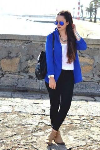 Топ белого цвета хорошо смотрится с облегающими брюками черного тона и пиджаком ярко-синего оттенка.