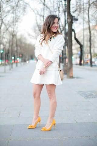Свитер на каждый день белого цвета, свободного покроя сочетается с юбкой белого тона.
