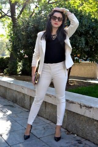 Костюм белого цвета, состоящий из двубортного пиджака и брюк облегающего покроя.
