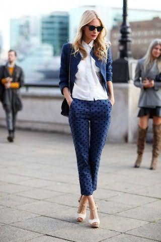 Рубашка в деловом стиле белого цвета дополняется укороченными брюками синего оттенка с гороховым принтом.