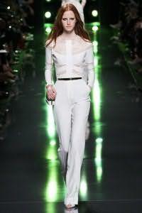 Вечерний костюм белого цвета, состоящий из блузы с кружевными вставками и брюк классического покроя от Elie Saab.