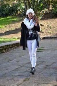 Вязаная шапка и шарф-хомут белого цвета составят гармоничный ансамбль со свитером черного оттенка.