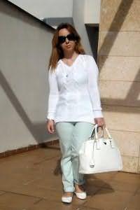 Объемная сумка и туфли белого цвета на плоской подошве сочетаются с брюками светло-бирюзового оттенка.