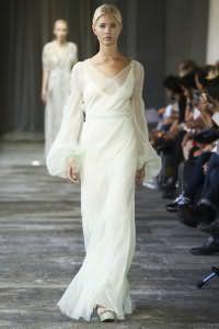 Платье белого цвета прямого силуэта, длиной в пол, с длинными прозрачными рукавами платформе от Luisa Beccaria.