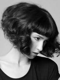 Волнистые волосы черного цвета на стрижке боб с прямой густой челкой дополнят естественный макияж глаз и светлая помада
