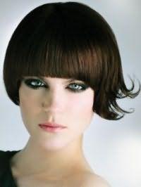 Каштановый цвет волос хорошо смотрится на стрижке боб с густой прямой челкой и гармонирует с вечерним макияжем в черных тонах для зеленых глаз и помадой розового цвета