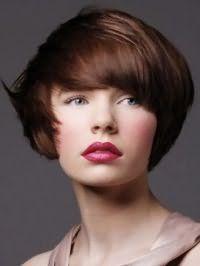 Великолепный образ со стрижкой боб на каштановых волосах, уложенной в хаотичные пряди, которая дополняется естественным макияжем серо-зеленых глаз, розовыми румянами и помадой красного оттенка