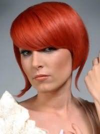 Огненно-рыжий цвет волос отлично выглядит на стрижке боб с удлиненными прядями и густой челкой на бок и гармонирует с макияжем глаз в серых тонах, румянами и помадой светлого коричневого оттенка