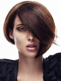 Креативная стрижка асимметричный боб с удлиненной челкой, дополнительным объемом на волосах каштанового цвета дополняется макияжем глаз в коричнево-золотой гамме и помадой розового оттенка