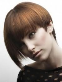 Волосы каштанового цвета с колорированными прядками рыжего оттенка хорошо смотрятся на асимметричной стрижке боб с густой челкой и дополняются макияжем глаз в виде стрелок, румянами и помадой естественного тона