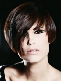 Асимметричная стрижка боб на волосах каштанового цвета создаст стильный образ в сочетании с макияжем в виде двойных стрелок для черных глаз и помадой натурального оттенка