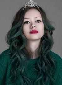 Креативное окрашивание в зеленый цвет для длинных кудрявых волос, оформленных в каскадную стрижку, гармонирует с вечерним макияжем зеленых глаз в черно-зеленой гамме и акцентом на ярко-малиновые губы