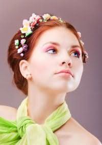 Вариант свадебного макияжа в нежно-розовой гамме для обладательниц рыжих волос, уложенных в прическу с разноцветными цветами