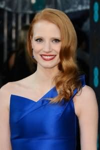 Праздничный образ для девушек с рыжими волосами создается с макияжем карих глаз в виде стрелок, использованием насыщенной красной помады и укладке локонов средней длины в ретро прическу