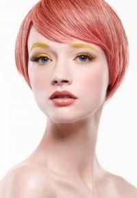 Идея образа с короткими волосами, дополненных косой челкой, креативного персиково-розового цвета в тандеме с ярким макияжем в желтых оттенках для девушек с голубыми глазами