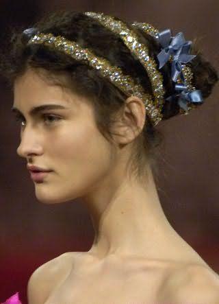Темно-русый цвет вьющихся волос хорошо смотрится на греческой прическе, зафиксированной длинной лентой со стразами и небольшими бантиками, и гармонирует с естественным макияжем для карих глаз и теплого цветотипа внешности