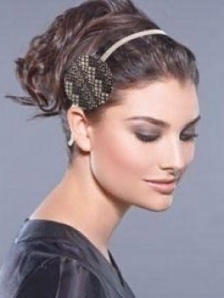Каштановый цвет волос великолепно выглядит в греческой прическе на среднюю длину в виде высокого хвоста с локонами, украшенной тонким серым ободком и сочетаются с макияжем в серых и коричневых тонах