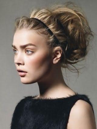 Стильная греческая прическа на длинные светлые волосы в виде хаотично уложенных локонов, зафиксированных тонким черным ободком, в сочетании с естественным макияжем глаз и помадой светло-коричневого тона
