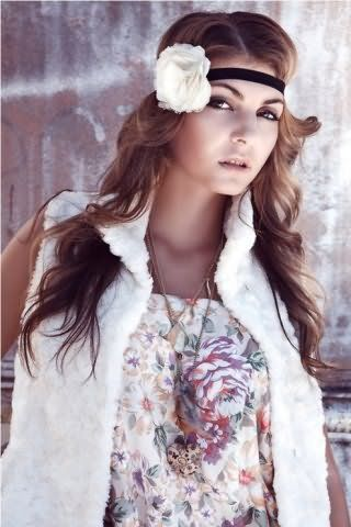 Греческая прическа в виде распущенных локонов, зафиксированных резинкой черного цвета с белым цветком, хорошо смотрится на длинных волосах светло-каштанового оттенка и сочетается с макияжем в коричневой гамме