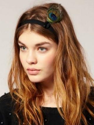 Длинные волосы карамельного оттенка отлично смотрятся в греческой прическе на распущенные пряди, украшенной резинкой с павлиньим пером, и дополняются естественным макияжем для зеленых глаз и помадой натурального тона