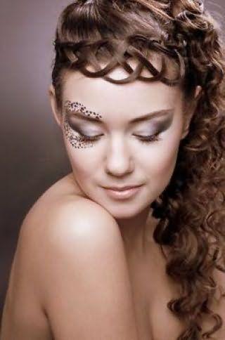 Креативная греческая прическа в виде высокого хвоста, уложенного в кудри, и ажурной косы вдоль лба дополнит вечерний образ девушки с каштановыми длинными волосами в сочетании с макияжем глаз серого тона