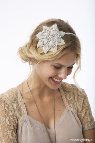 Волнистые длинные волосы пшеничного оттенка, уложенные в греческую прическу с тонким ободком, декорированным цветком серебристого оттенка, дополнят образ девушки с естественным макияжем
