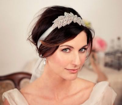 Естественный макияж серо-зеленых глаз гармонирует со светлым блеском для губ и дополняет свадебную прическу с лентой, декорированной стразами, на волосах каштанового оттенка