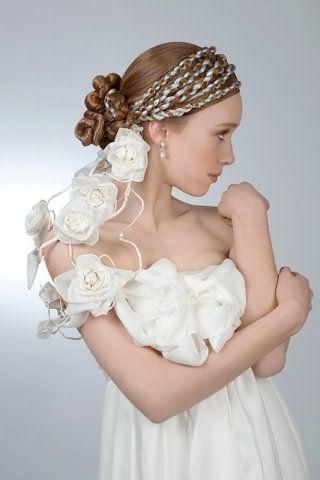 Нежный свадебный образ в виде гармоничного сочетания макияжа в естественных тонах и прически с лентами, вплетенными в косы вокруг головы, серебристого оттенка на длинных волосах светло-русого цвета