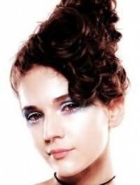 Великолепным решением для кудрявых волос каштанового оттенка станет высокая греческая прическа, собранная на макушке, с челкой, дополненная голубыми тенями для карих глаз