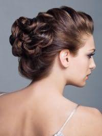 Макияж глаз в стиле смоки айс сочетается с помадой натурального оттенка и дополняет вечерний образ девушки с каштановыми волосами, собранными в высокую греческую прическу с плетением