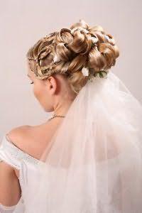 Роскошная греческая прическа со сложным плетением и локонами, уложенными на затылке и декорированными белыми цветами, дополнит свадебный образ блондинки с теплым цветотипом внешности