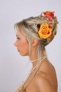 Длинные волосы пепельного оттенка хорошо смотрятся в высокой греческой прическе с челкой, которую украшают цветы оранжевого и розового цвета и гармонично дополняет макияж в натуральном стиле