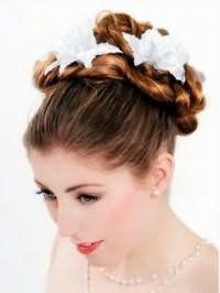 Нежная греческая прическа, уложенная жгутами и украшенная белыми цветами, хорошо смотрится на длинных волосах светло-каштанового оттенка и подходит для свадебного образа