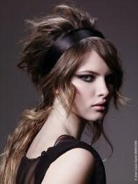 Греческая прическа на длинных волосах русого цвета с небольшим начесом, украшенная атласной лентой черного оттенка, гармонирует с макияжем глаз в черных тонах и светло-розовой помадой