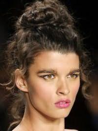 Греческая прическа на длинные вьющиеся волосы, уложенные на макушке, обретает особый шарм в сочетании с выбившимися прядями, естественным макияжем карих глаз и помадой розового оттенка