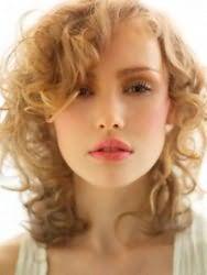 Ультрамодная укладка стрижки с удлиненной челкой для вьющихся волос светло-русого тона отлично дополнит как повседневный, так и вечерний образ