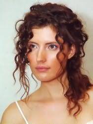Повседневная прическа на кудрявые волосы средней длины в виде низкого хвоста с оставленными прядками удлиненной челки, которые выгодно обрамляют овальное лицо