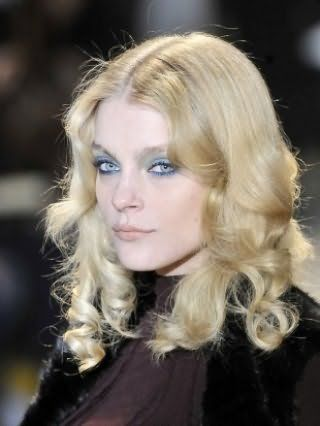 Блондинкам с круглым лицом и волосами средней длины отлично подойдет укладка в форме локонов от середины лица в тандеме с макияжем в зелено-голубых оттенках